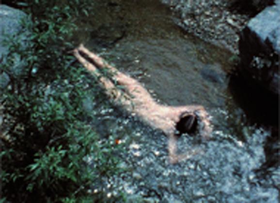"""Ana Mendieta still from """"Creek"""" 1974, super 8 film, color, silent. Courtesy BAMPFA."""